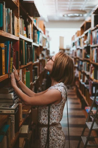A woman browses bookshelves