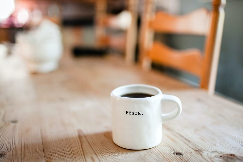 A white cup with begin written on it